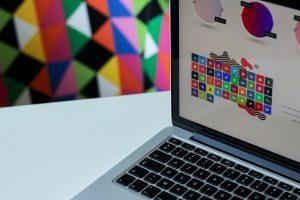 Srebrny laptop z kolorowymi grafikami na ekranie - czym różni się grafika wektorowa od rastrowej?